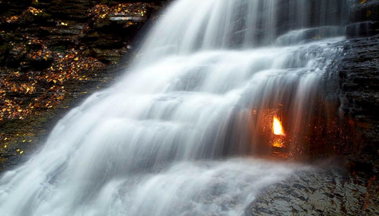 La misteriosa fiamma che brucia sotto la cascata